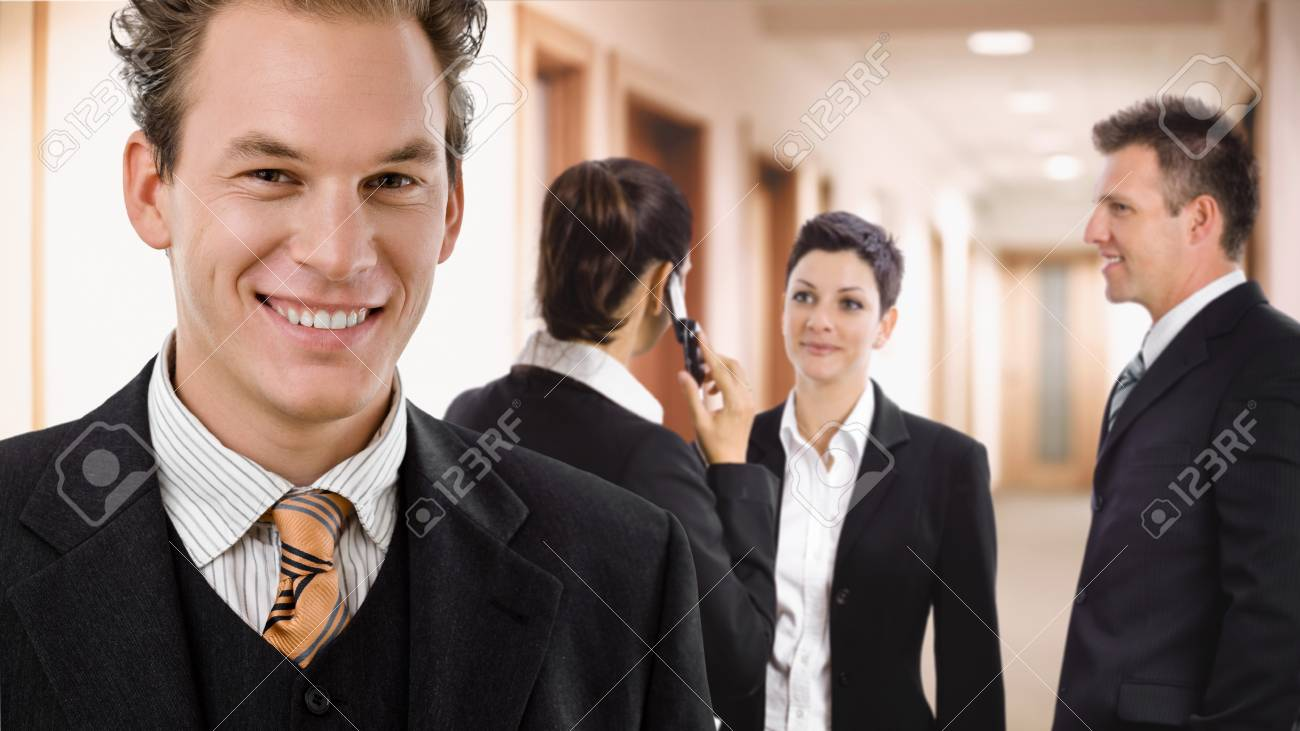 Happy businessman smiling in front, other businesspeople talking in the background. Stock Photo - 7488074
