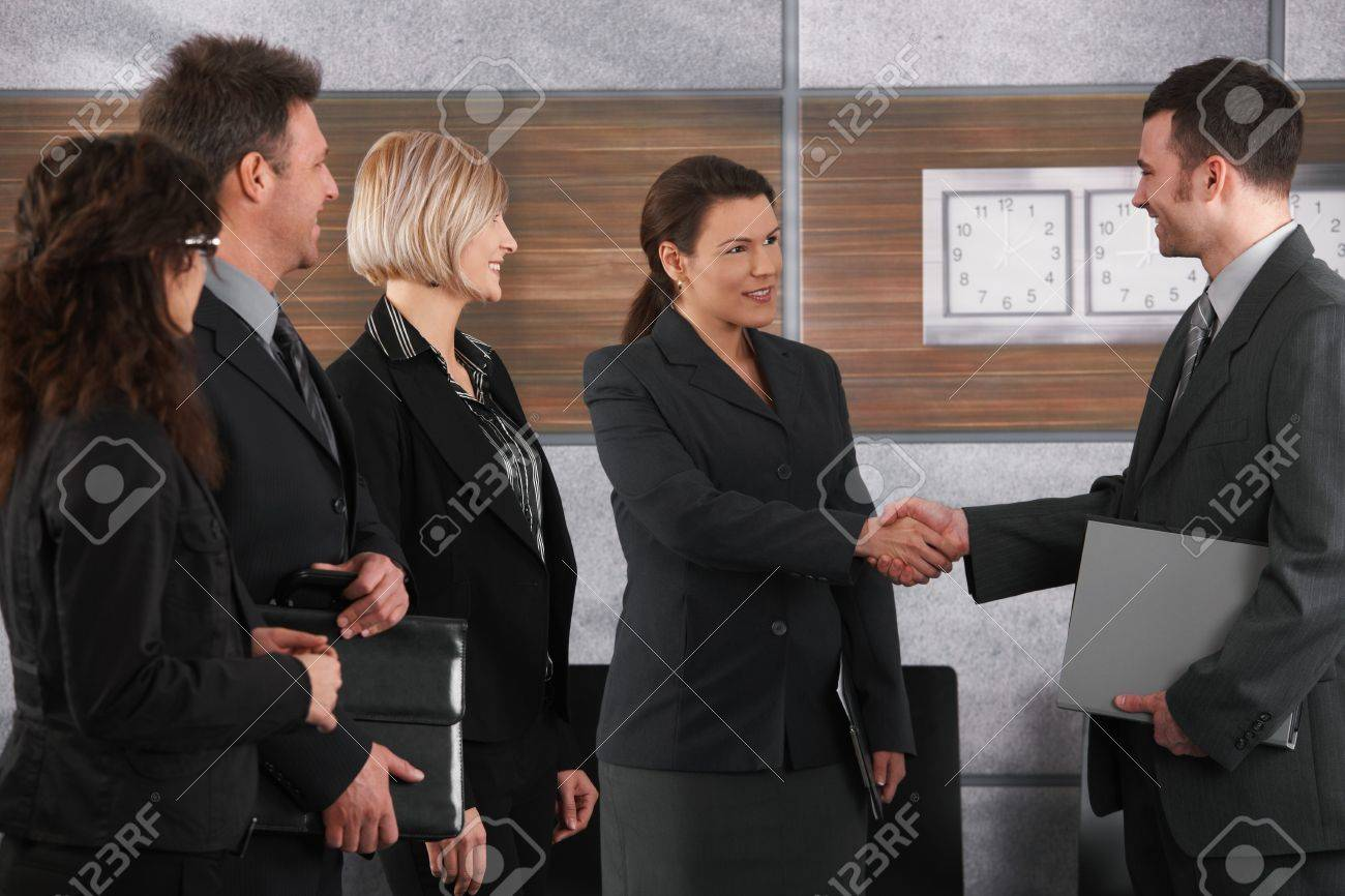 Smiling businessman and businesswoman shaking hands in office. Stock Photo - 7520478