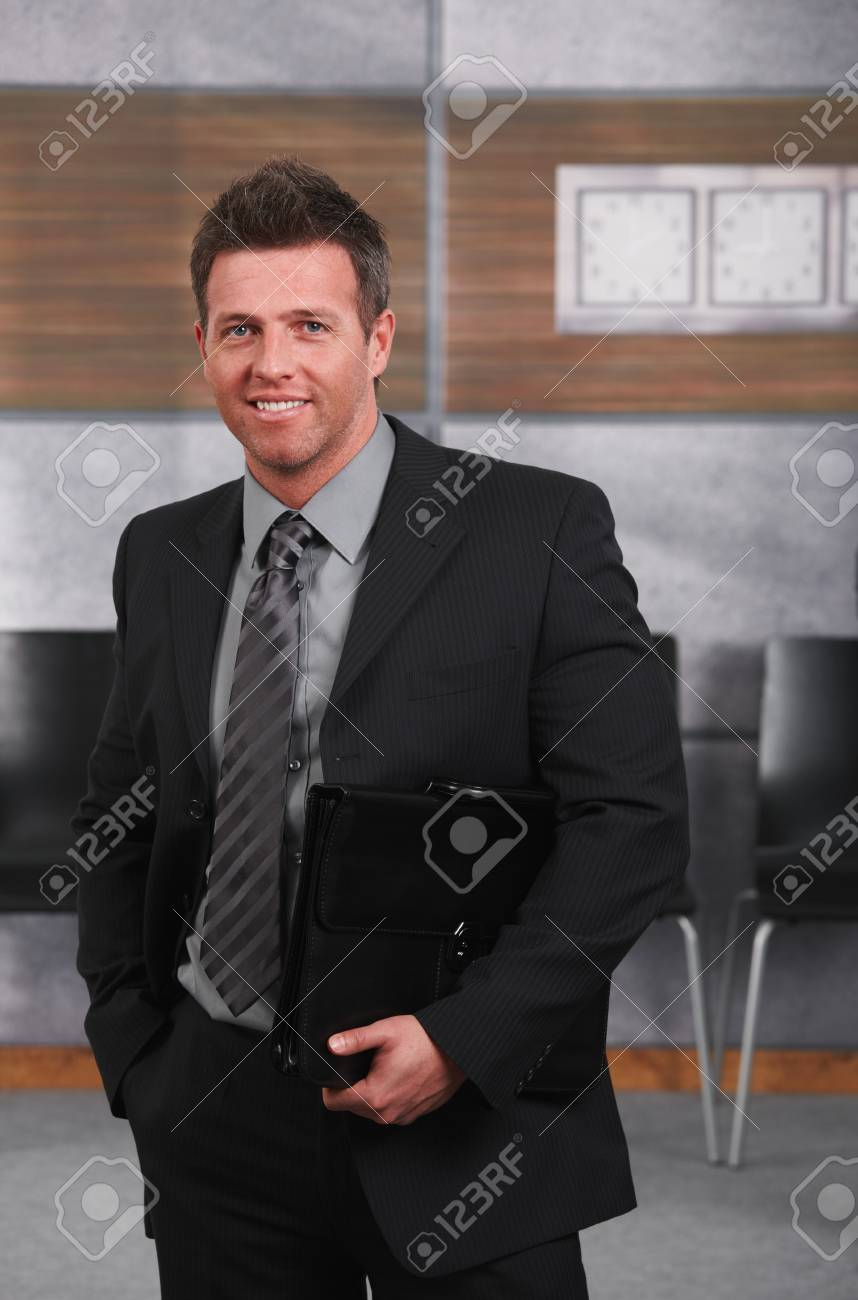 Portrait of happy businessman standing on office corridor looking at camera, smiling. Stock Photo - 7520462