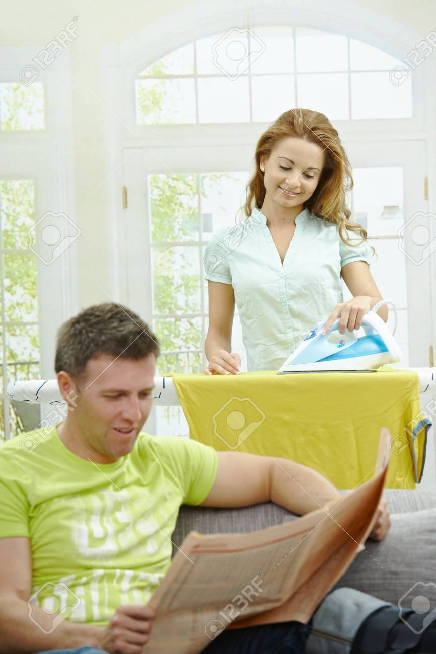 Husband sitting at couch reading news, wife ironing in the background, smiling. Selective focus on woman. Stock Photo - 7563473