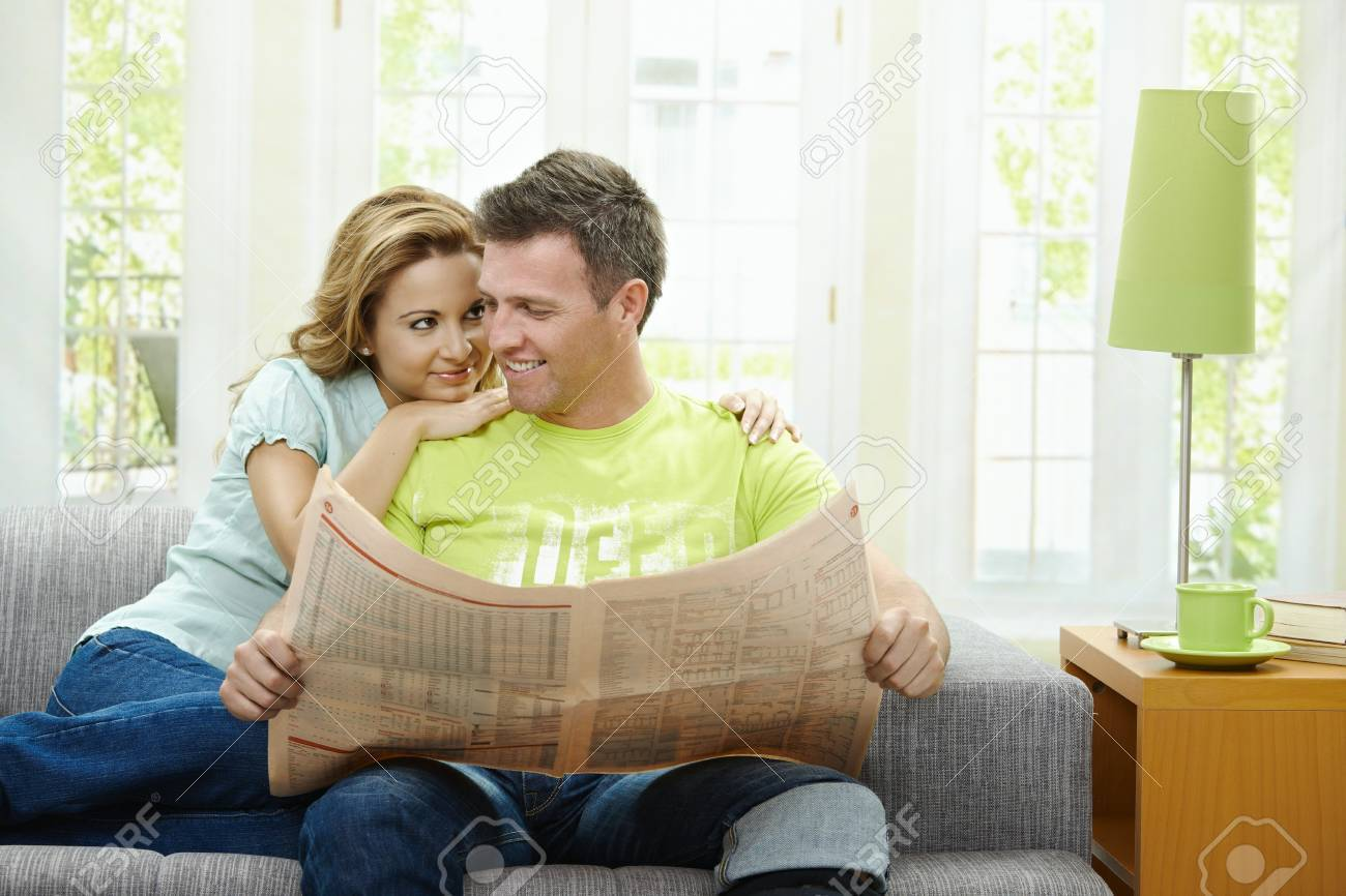 Love couple reading newspaper together on couch at home, looking at camera, smiling. Stock Photo - 7563506