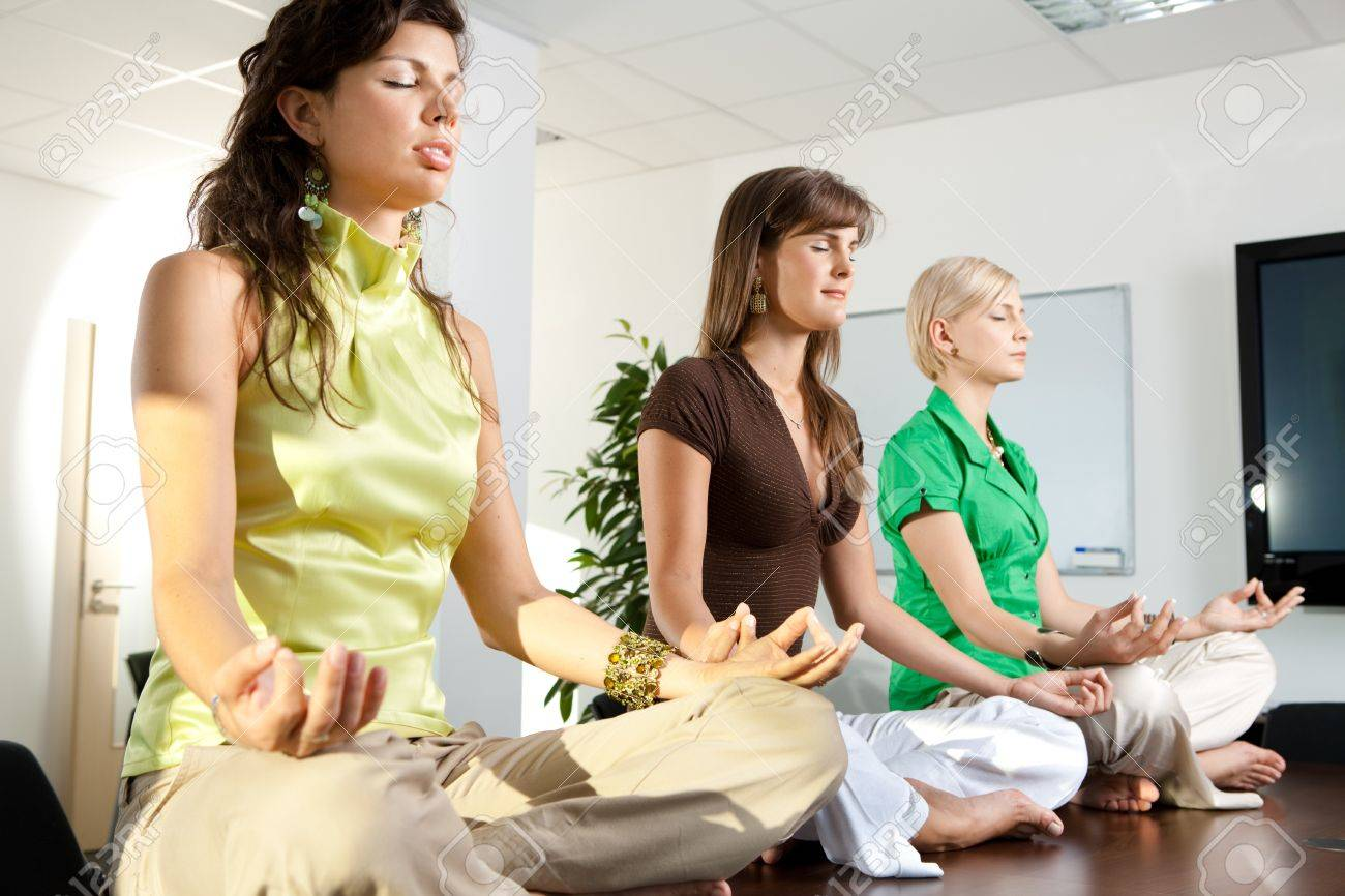Young businesswomen sitting in lotus position on meeting room table. Stock Photo - 7628384