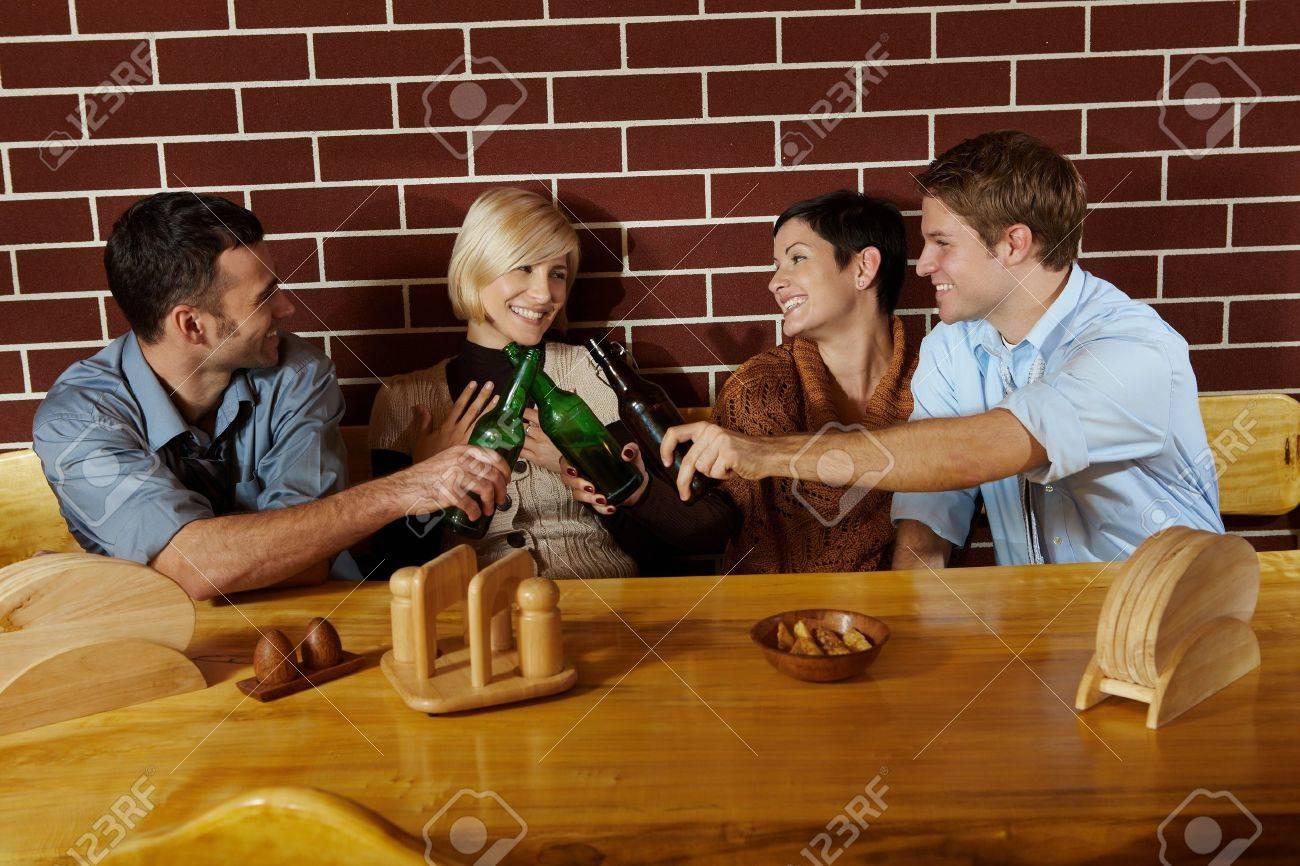Friends having fun at bar, sitting together at table, having beer, laughing. Standard-Bild - 7628849