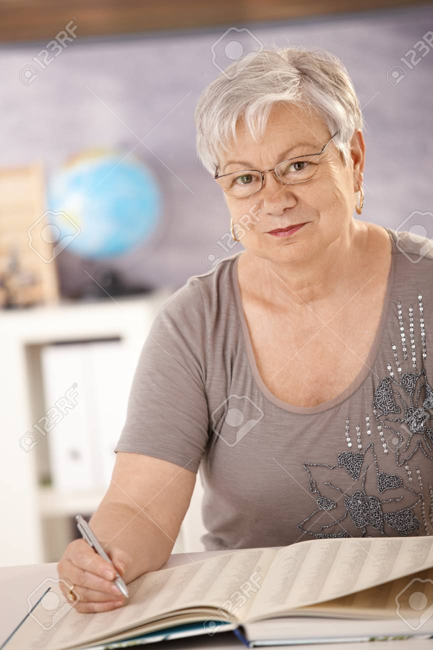 Portrait of senior teacher sitting at desk in classroom, searching in a book, looking at camera. Stock Photo - 7639404