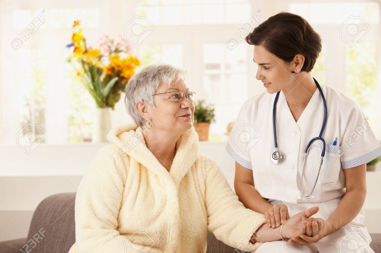 Nurse measuring heartbeat of senior woman at home. Looking at camera, smiling. Stock Photo - 7639238