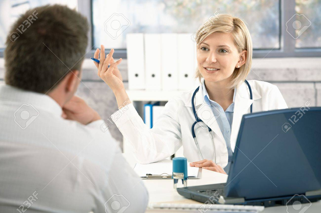 Confident female doctor discussing diagnosis with patient in office, smiling. - 7653600