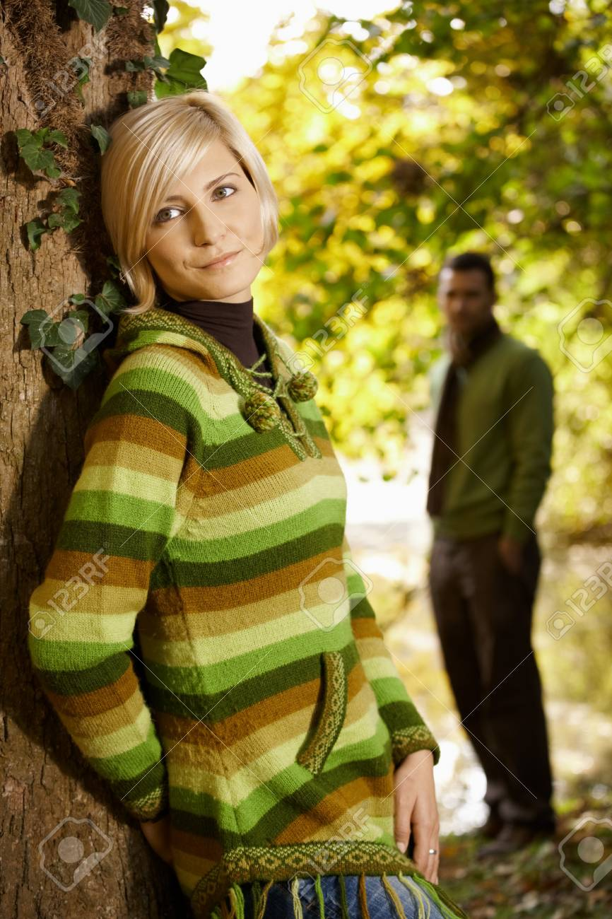 Outdoors portrait of happy young woman leaning to tree trunk in autumn park, smiling. Stock Photo - 7718277