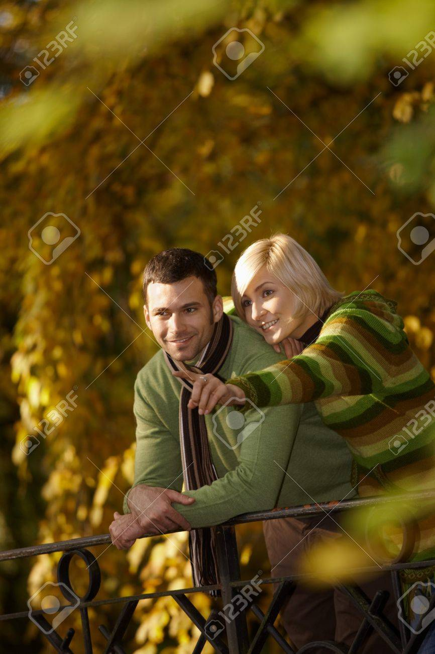 Outdoors portrait of happy couple standing in autumn park, woman showing something to man, smiling. Stock Photo - 7718240