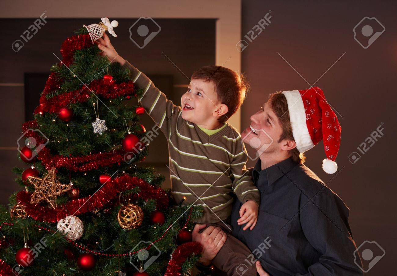 Dad christmas ornament - Dad Helping Son To Decorate Christmas Tree Boy Putting Up The Top Ornament Smiling