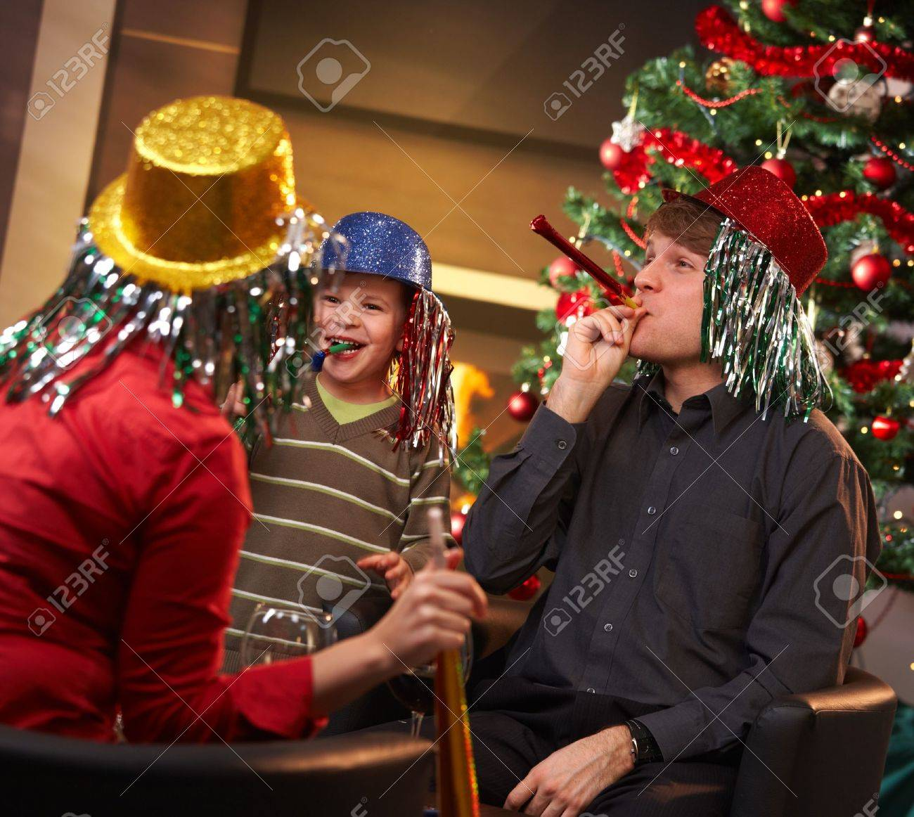 Happy family of three celebrating in new year eve hat at home. Stock Photo - 7791771
