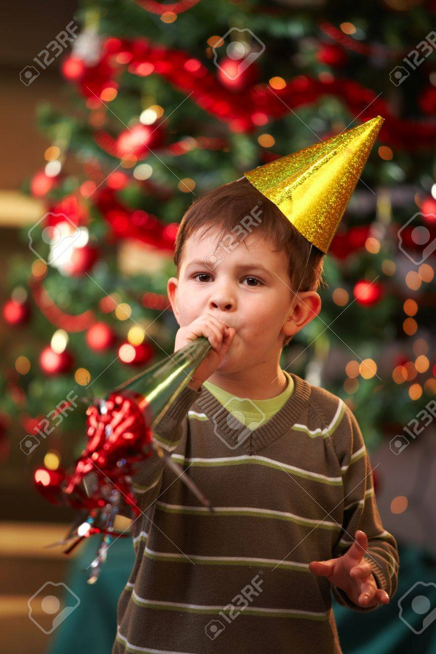 Little boy in new year's eve hat blowing horn, looking at camera. Stock Photo - 7791818