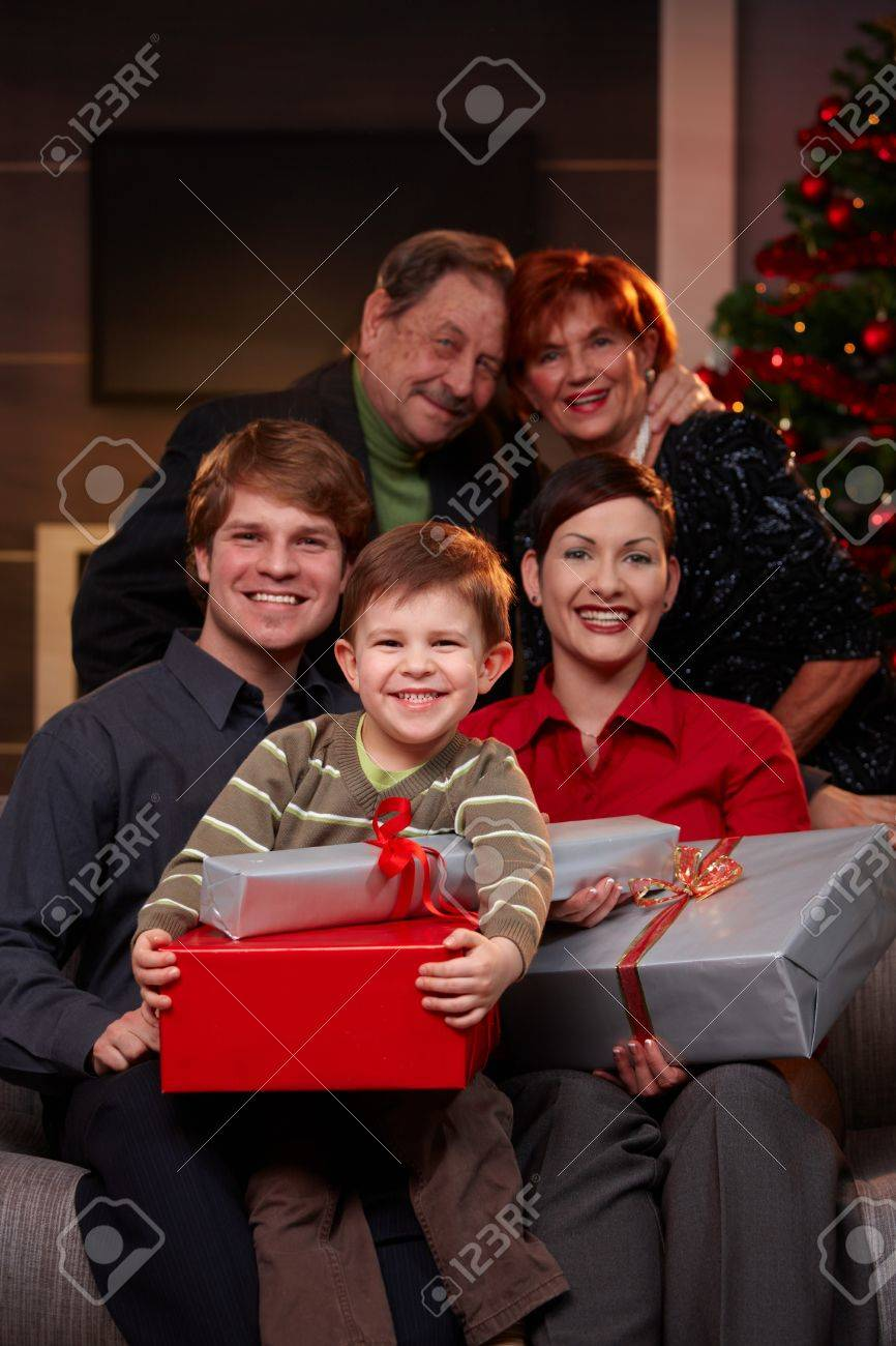 Portrait of happy family together with grandparents at christmas eve, holding presents, smiling. Stock Photo - 7791895