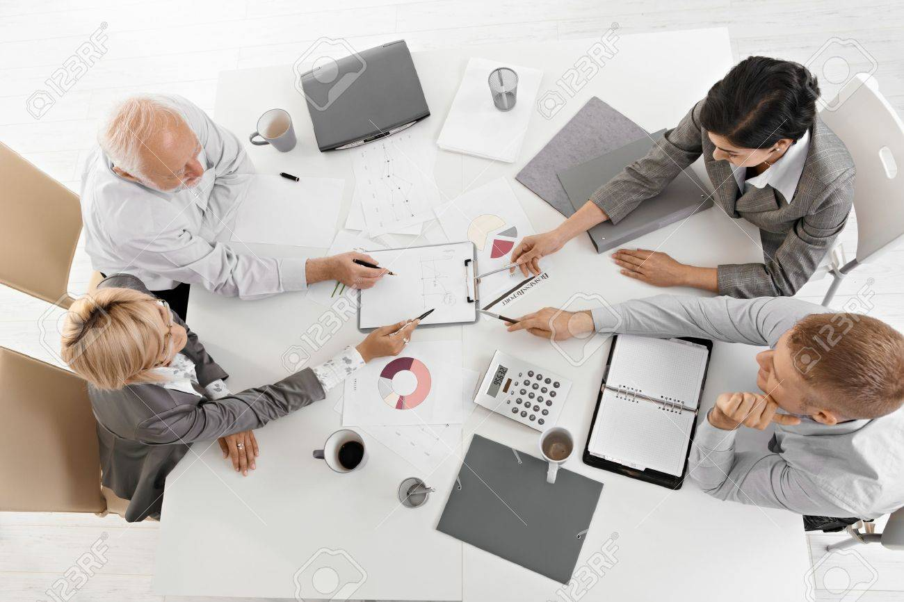 Businesspeople working together at meeting, discussing document on clipboard, high angle view. Stock Photo - 7791893