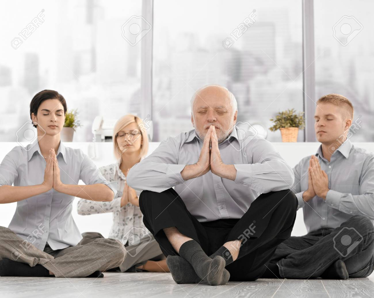 meditation in office. businesspeople doing meditation in office with closed eyes hands put together concentrating stock i