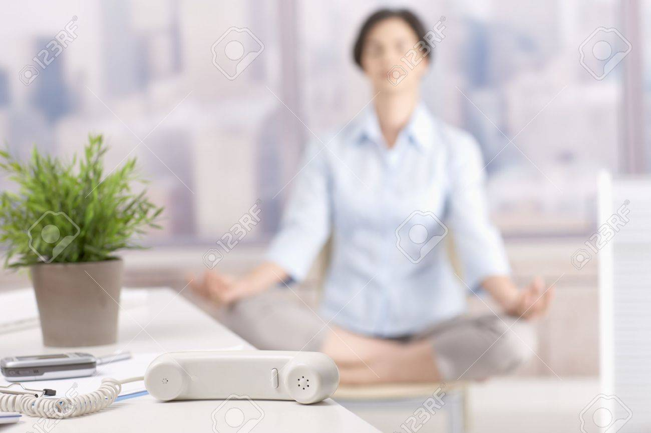 Landline phone put aside in skyscraper office, woman meditating in background. Stock Photo - 7792009