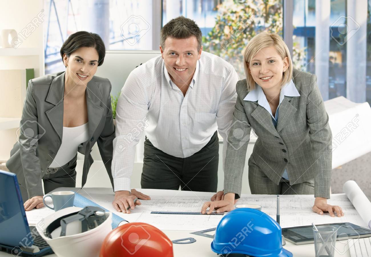 Smiling architect team standing in office with work plan, looking at camera. Stock Photo - 7792167