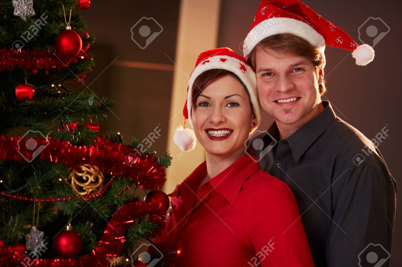 Portrait of happy young couple wearing santa claus hat, celebrating christmas, smiling. Stock Photo - 7792287