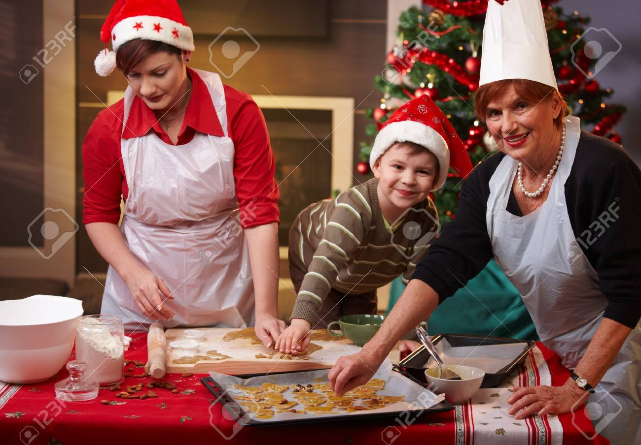 Grandmother, mum and son making christmas cake together at home, smiling. Stock Photo - 7792225