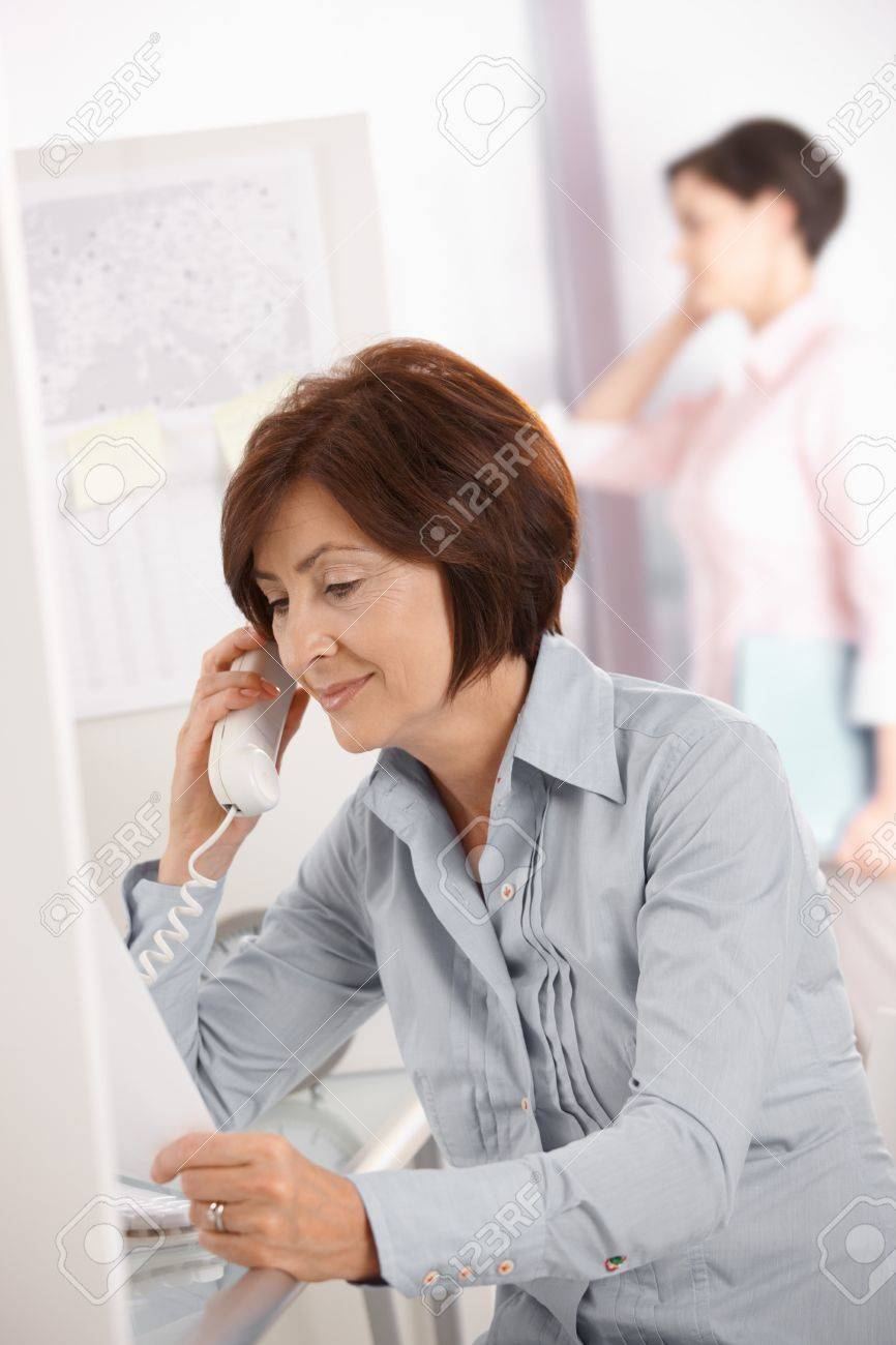 Mature office worker woman using landline phone, smiling, coworker using mobile phone in background. Stock Photo - 7792180
