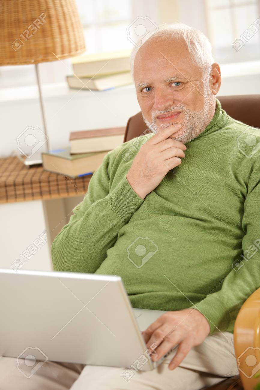 Portrait of smiling senior man with laptop computer at home. Stock Photo - 7899228