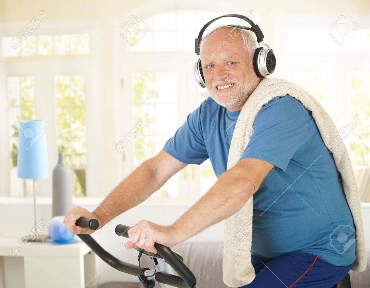 Active pensioner doing spinning on bike at home while listening to music, smiling at camera. Stock Photo - 7899175