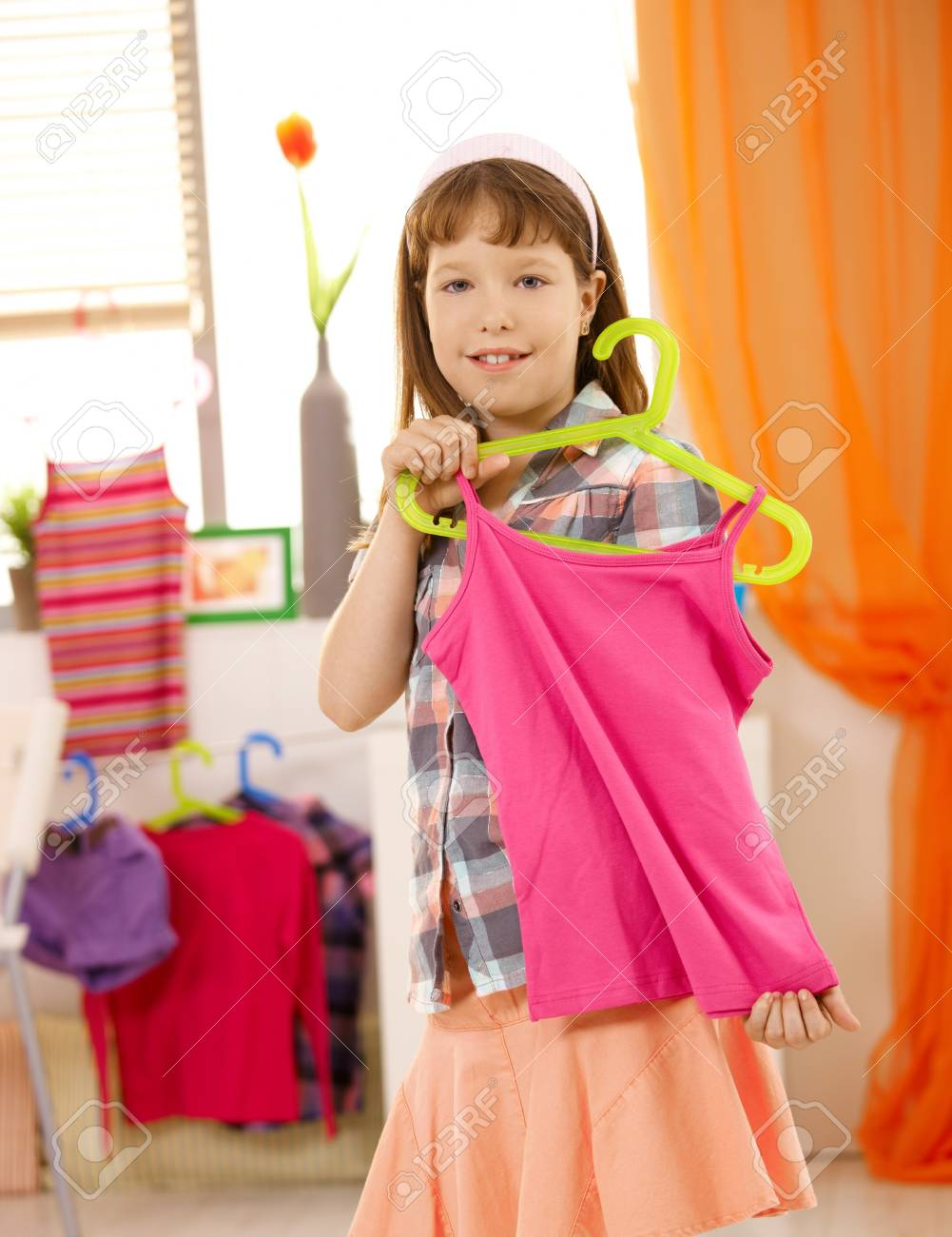Schoolgirl showing nice top on hanger, smiling at camera. Stock Photo - 7899233