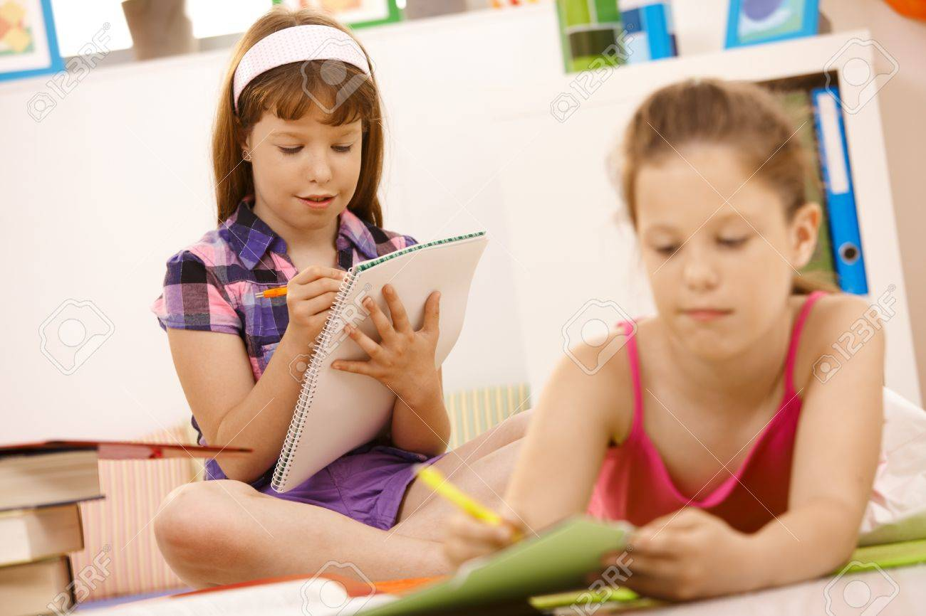 Schoolchildren writing into booklet at home, doing homework. Stock Photo - 7899215
