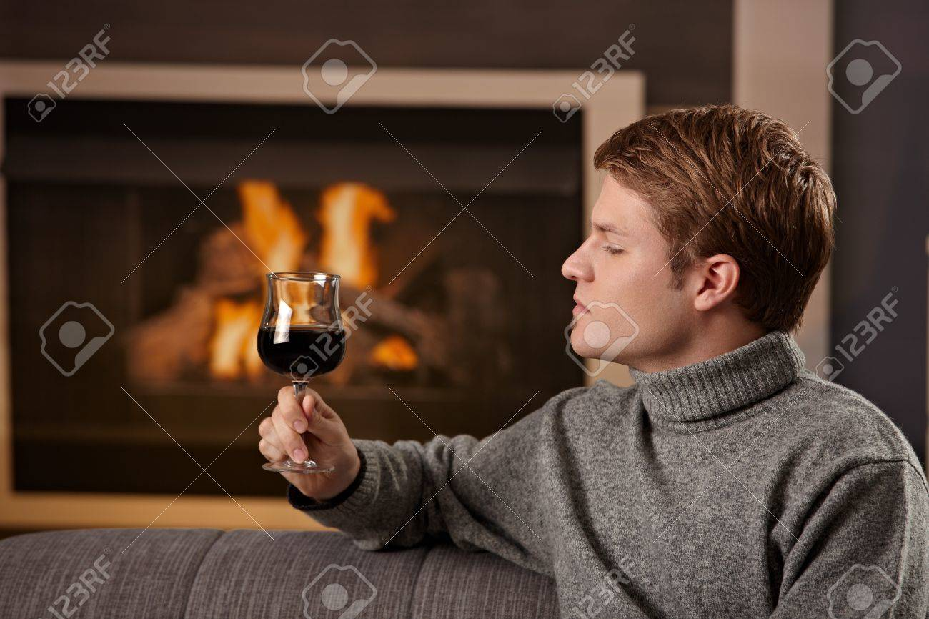 Young Man Sitting On Sofa At Home On A Cold Winter Day In Front ...
