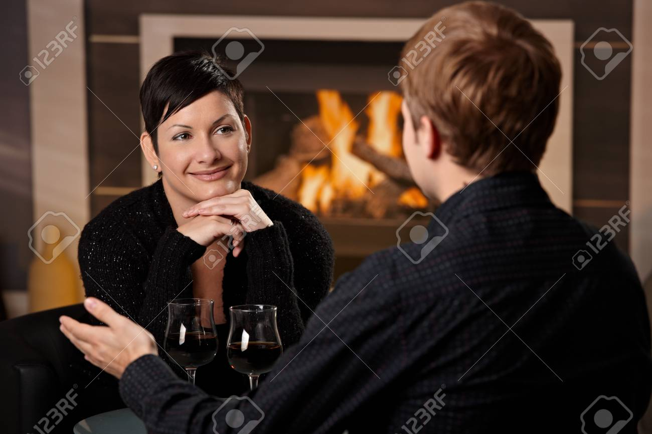 Young romantic couple dating, sitting in front of fireplace at home, drinking red wine. Stock Photo - 7962020