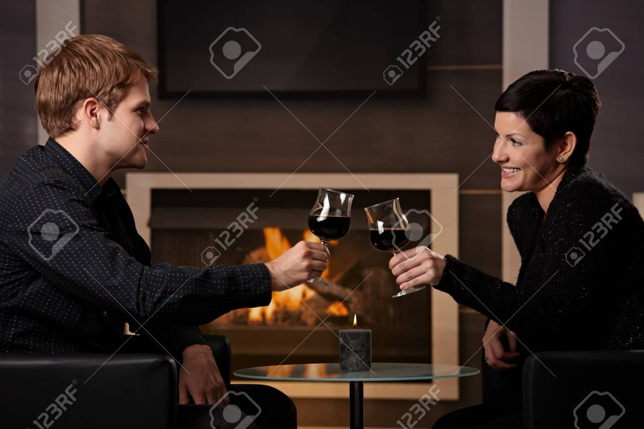Young romantic couple dating, sitting in front of fireplace at home, drinking red wine. Stock Photo - 7962022