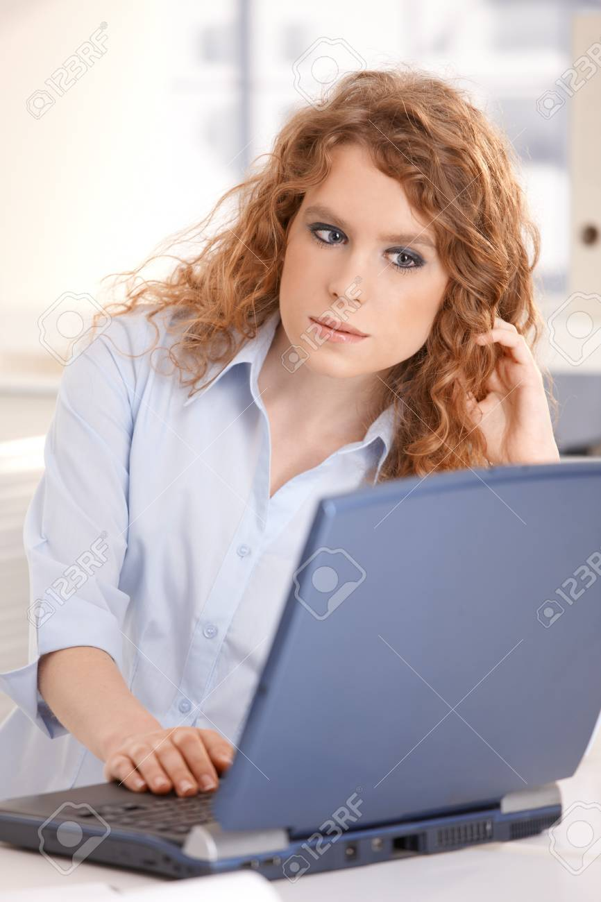 Young attractive woman using laptop browsing Internet at home. Stock Photo - 8083475