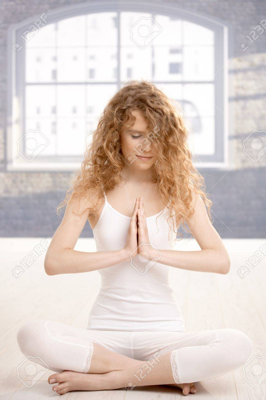 Young attractive woman practicing yoga, meditating in prayer pose, eyes closed, sitting on floor. Stock Photo - 8083457