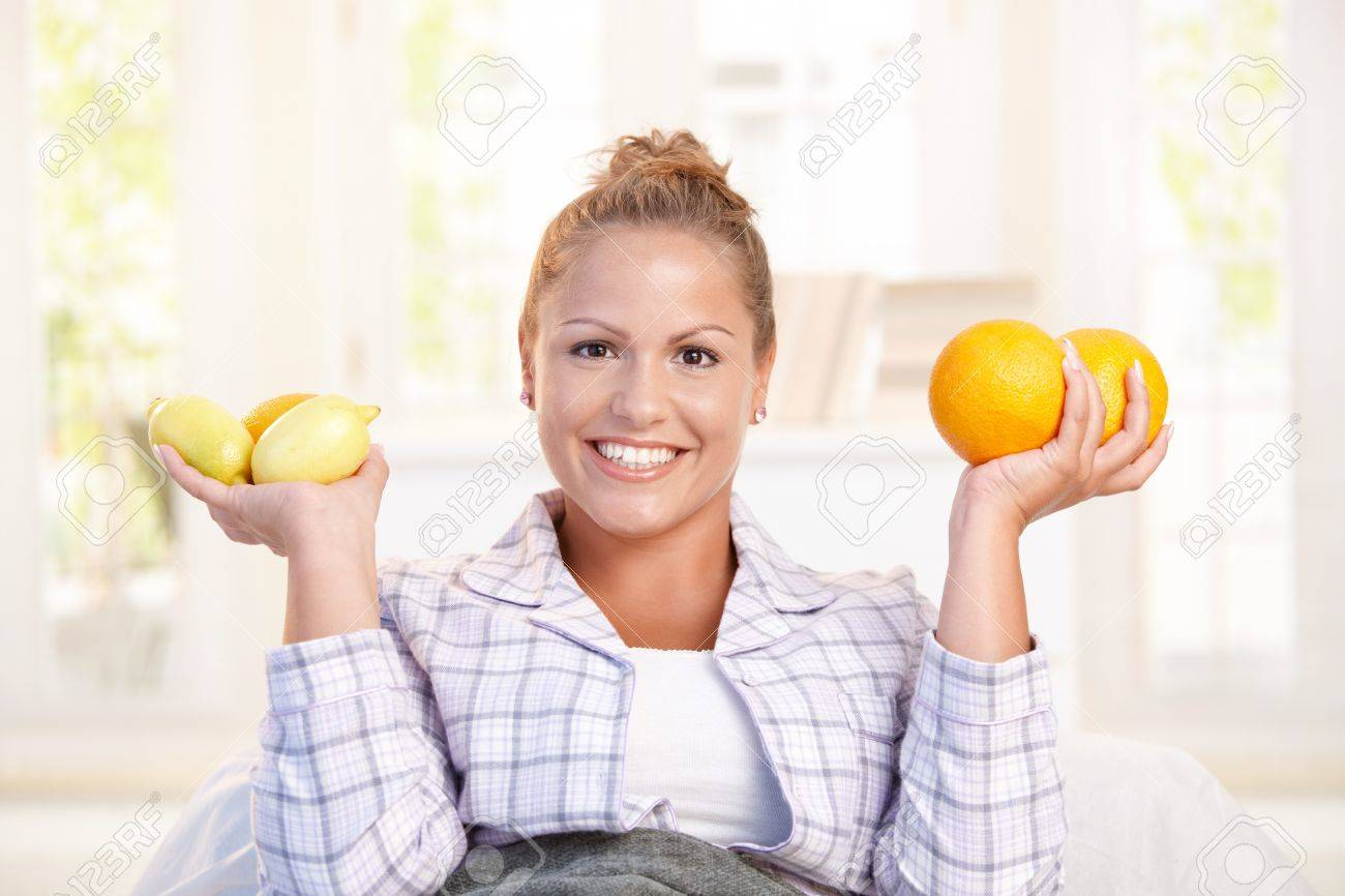 Portrait of young woman holding lemons and grapefruits in her hand smiling, living healthy. Stock Photo - 8121259