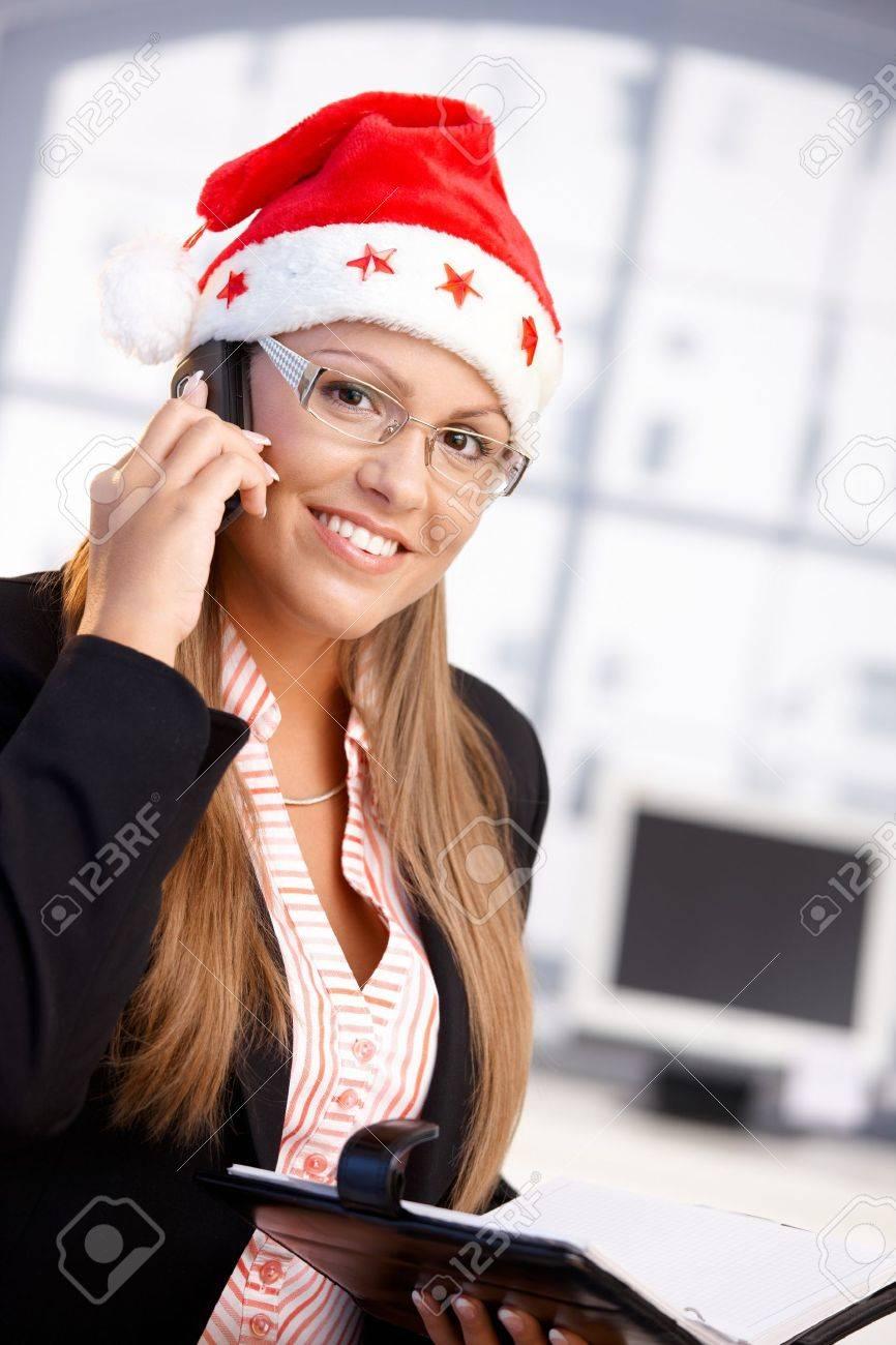 Pretty female wearing santa hat, holding organiser, using mobile, smiling in office. Stock Photo - 8121298