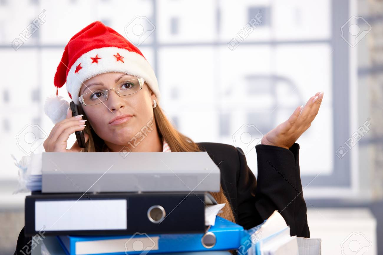 Young female in santa hat sitting in office behind folders, using mobile, having trouble. Stock Photo - 8121233