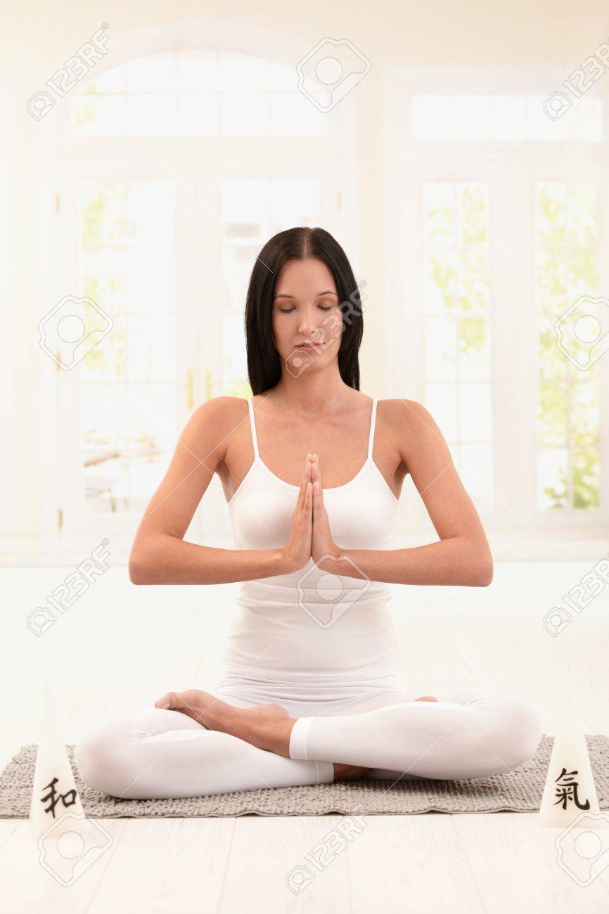 Young woman wearing white doing yoga exercise with closed eyes. Stock Photo - 8121384