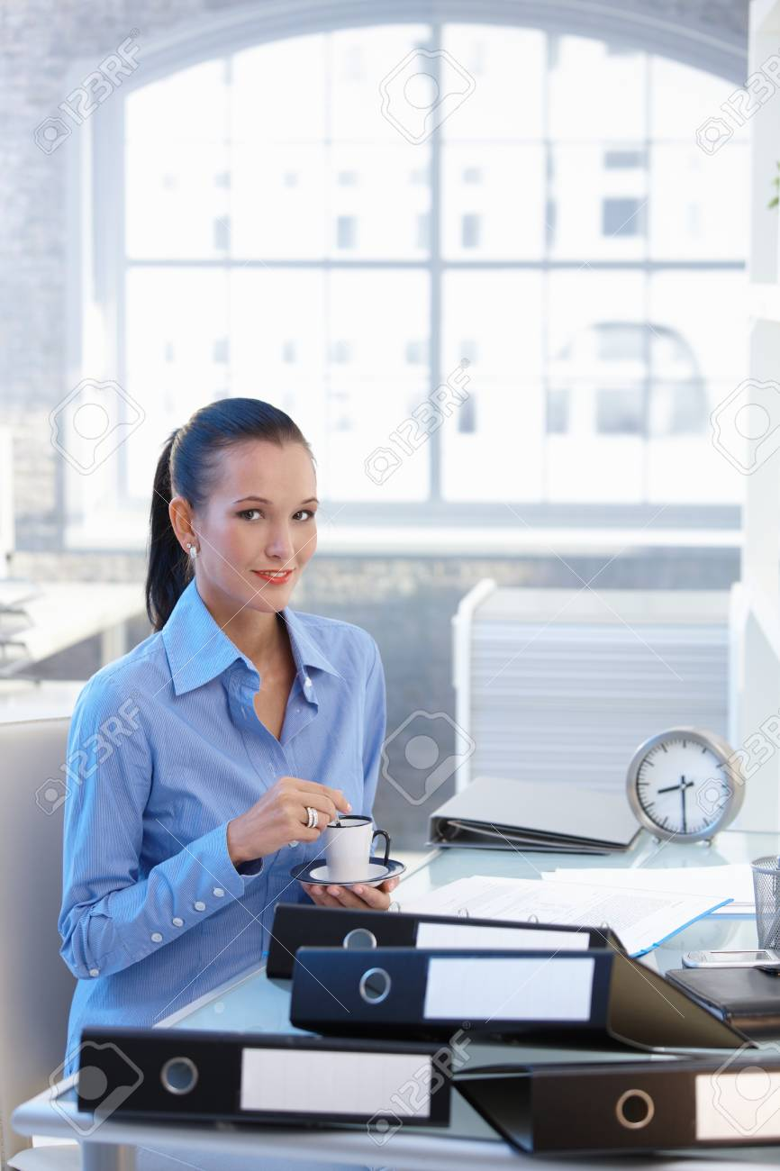 Portrait of smiling young businesswoman having coffee sitting at desk in office. Stock Photo - 8118117