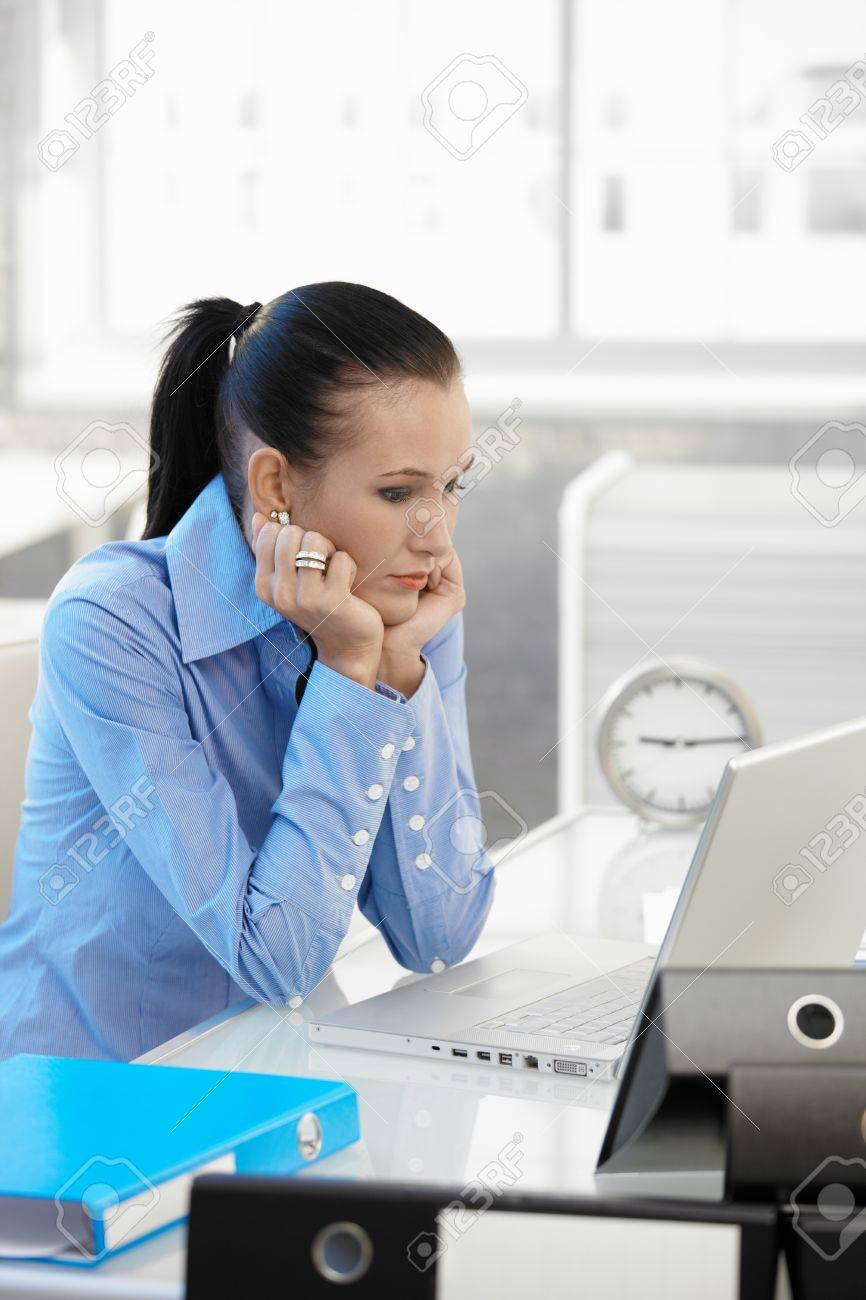 Troubled businesswoman concentrating on computer work at desk in office, looking at laptop screen. Stock Photo - 8121624