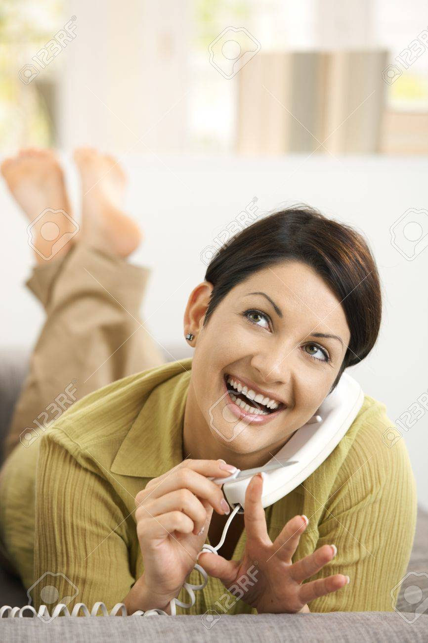 Happy woman filing nails while chatting on phone, lying on sofa, smiling. Stock Photo - 8121713