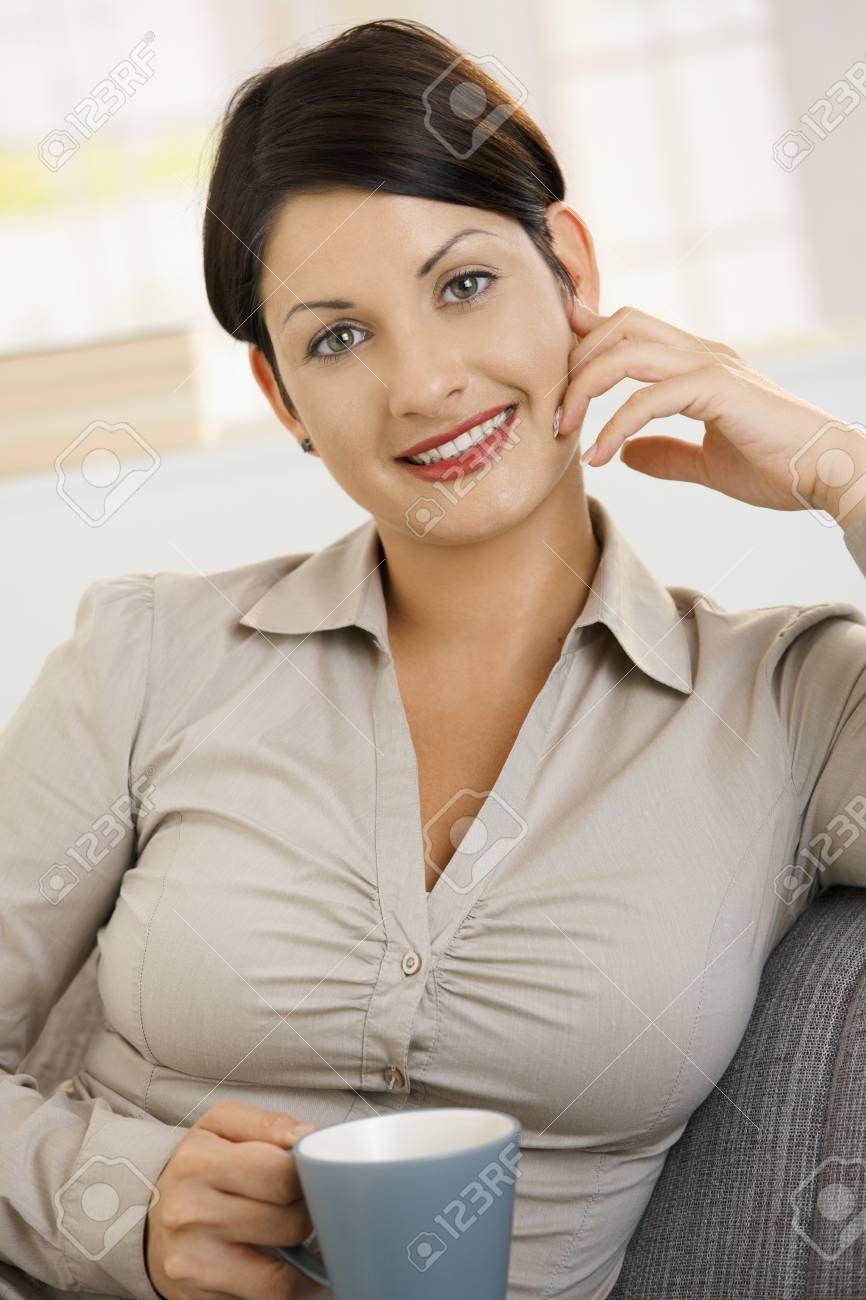 Closeup portrait of happy young woman drinking tea at home, smiling. Stock Photo - 8121767