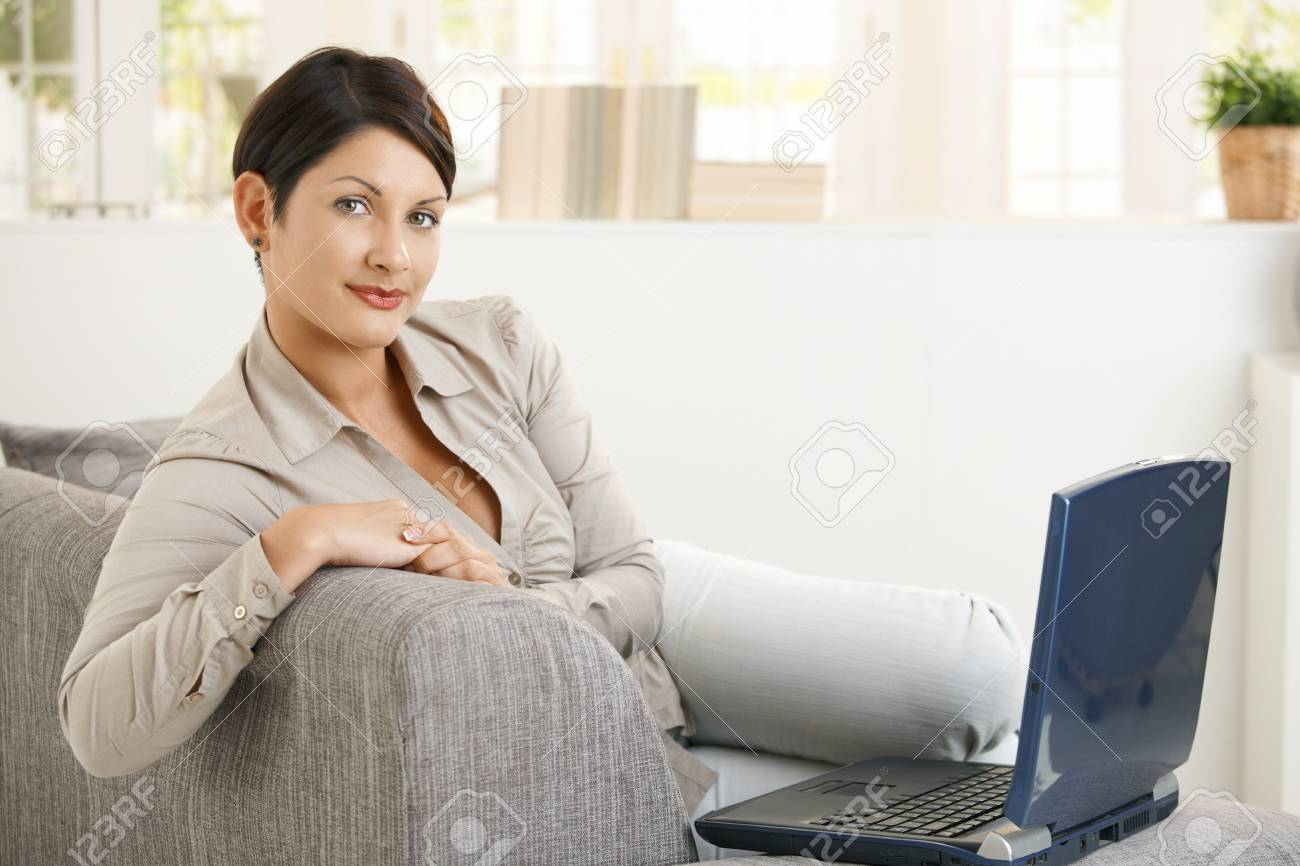 Happy young woman lying on sofa at home, browsing internet, smiling. Stock Photo - 8141694