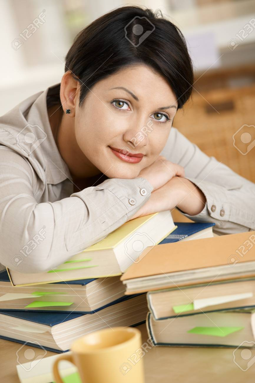 Tired young woman learning at home, resting on pile of books. Stock Photo - 8141673