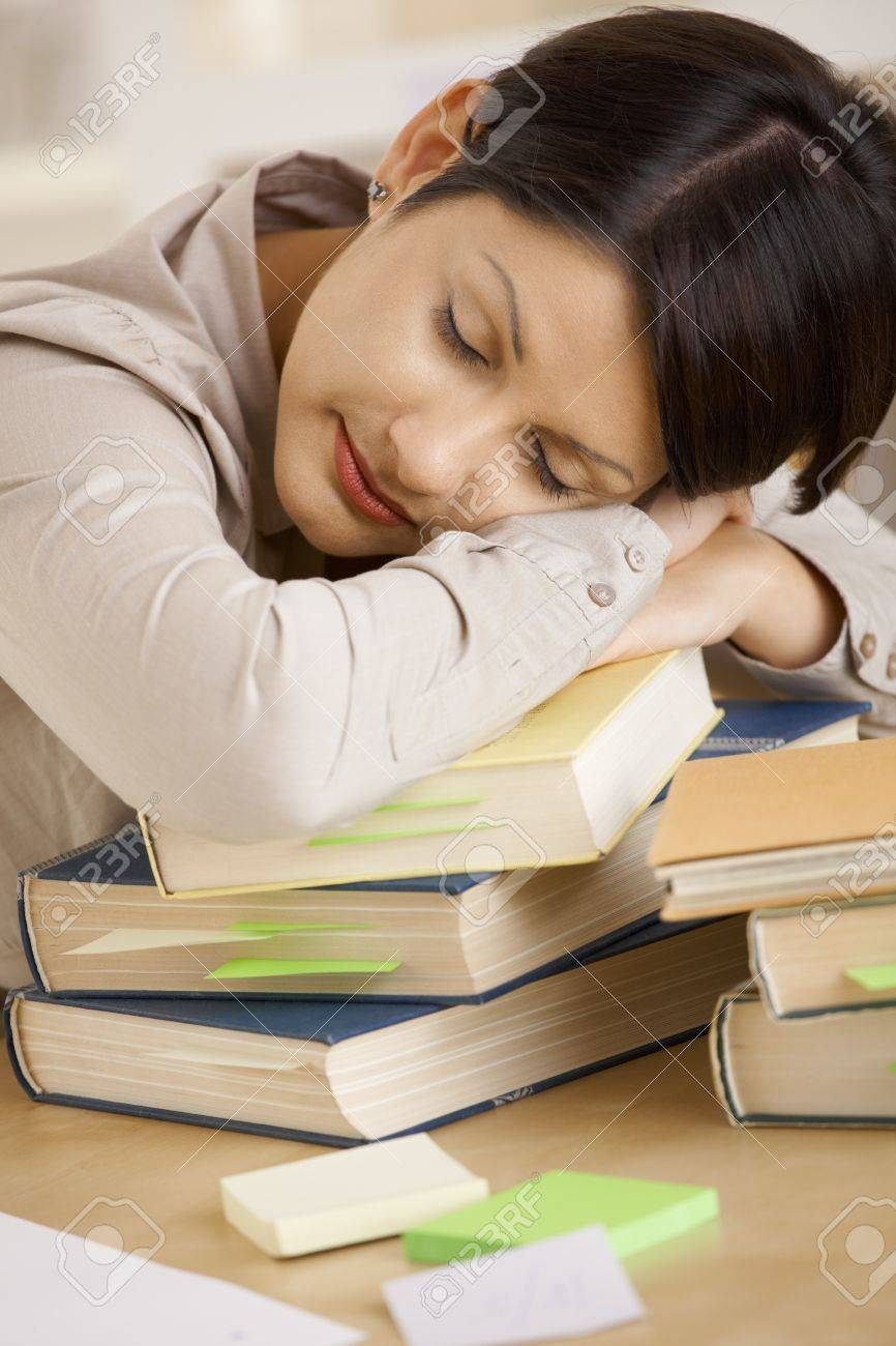 Closeup portrait of tired college student sleeping on pile of books on desk. Stock Photo - 8141666