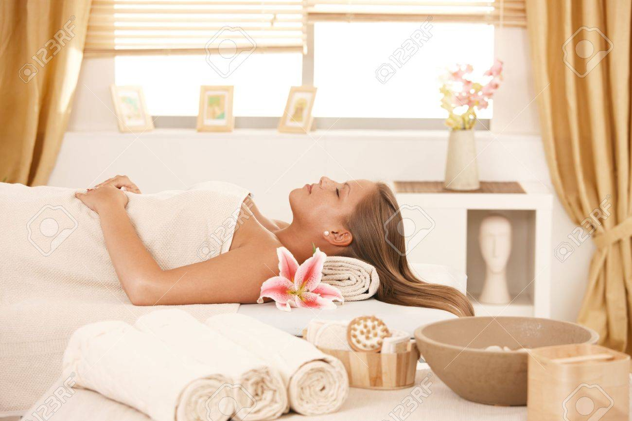 Attractive young woman resting with eyes closed on massage bed at spa. Stock Photo - 8305194