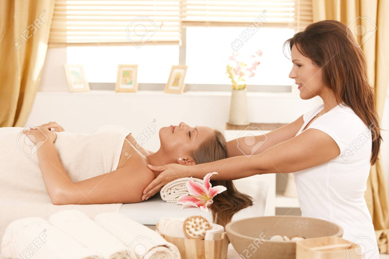 Young woman lying on bed in day spa, getting massage. Stock Photo - 8141727