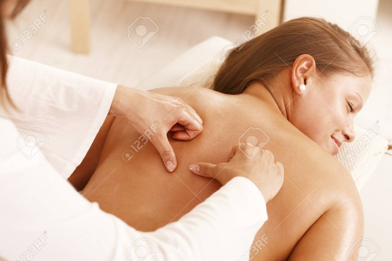 Smiling young woman getting back massage in day spa. Stock Photo - 8141803