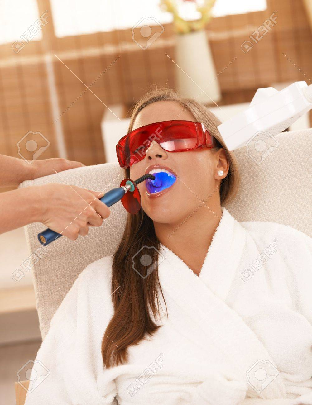 Young woman getting laser tooth whitening treatment at spa. Stock Photo - 8141730