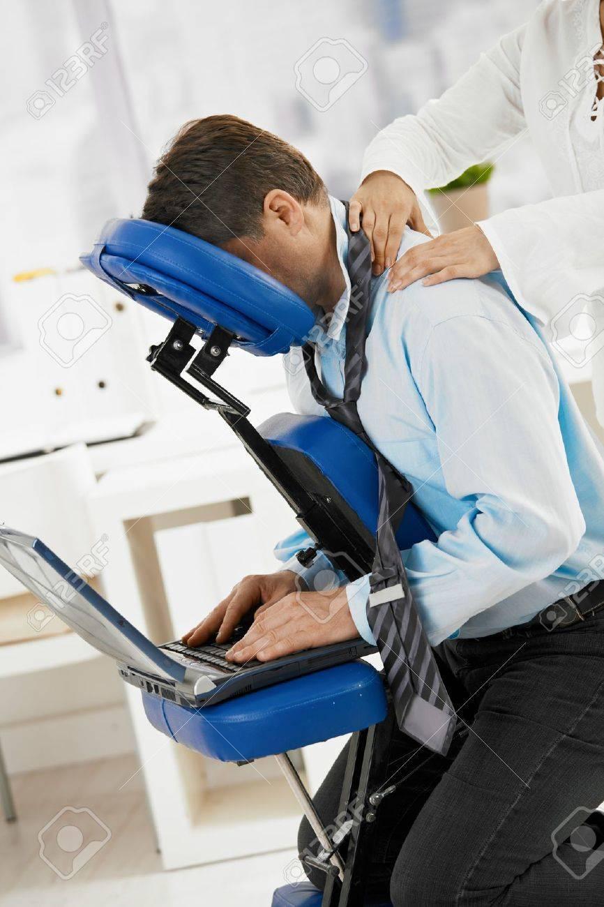 Businessman sitting on massage chair, getting back massage. Stock Photo - 8141756