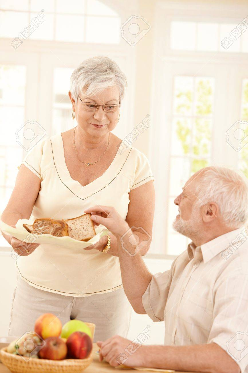 Smiling older wife serving bread for breakfast to husband sitting at kitchen table. Stock Photo - 8250819
