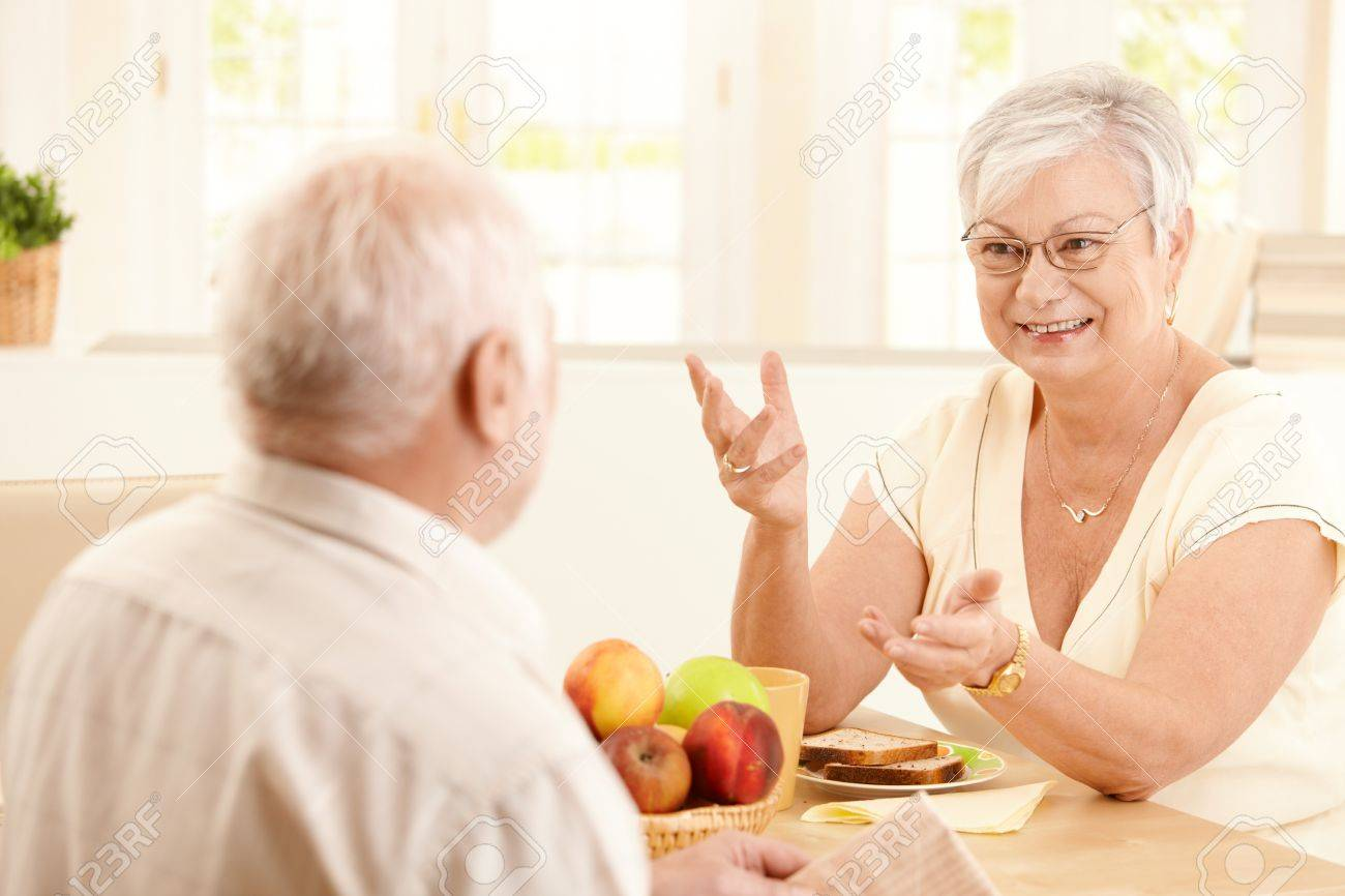 Elderly cheerful wife chatting to husband at breakfast table, gesturing, smiling. Stock Photo - 8250802